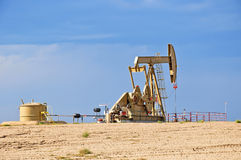 Crude Oil Pump Jack Against a Blue Sky Stock Photos