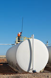 Crude oil tank. White storage tank of crude oil at field; worker dipping the tank to check the oil level, Cooper Basin, South Australia Stock Photos