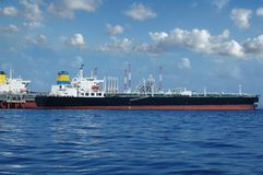Crude oil tanker is loading in the port. On the background of clouds Royalty Free Stock Images