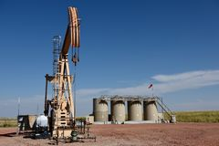 Crude oil well site pump jack and production storage tanks in the Niobrara shale royalty free stock images