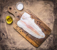 Crude Pangasius on a cutting board with butter and salt wooden rustic background top view close up Royalty Free Stock Photos
