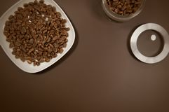 Crude pine nuts in plate and in can on brown background top view. Organic and healthy food.  stock photos