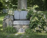 A Crude Stone Bench with Flowers and Plants Surrounding Royalty Free Stock Image