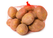 Crude unpeeled potatoes in the mesh bag Royalty Free Stock Images