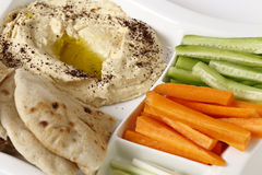 Crudites and hummus dip. A dip tray with hummus, bread, carrot sticks, celery and cucumber Royalty Free Stock Photo