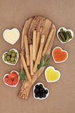 Crudites Selection. With bread sticks, mayo and chili dips, olives, oil, gherkins and tomatoes on an olive wood   board Stock Photography
