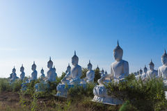 crudo di stato bianco di Buddha sul fondo del cielo blu Immagini Stock