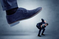 Cruel boss tramping his employee. Big foot trying to crush small man who is afraid of that stock photography