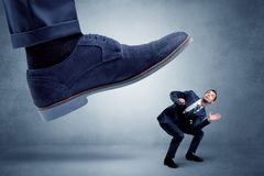 Cruel boss tramping his employee. Big foot trying to crush small man who is afraid of thatn royalty free stock photo