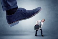 Cruel boss tramping his employee. Big foot trying to crush small man who is afraid of thatn royalty free stock image