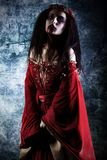 Cruel demon. Portrait of a bloodthirsty female vampire Stock Images