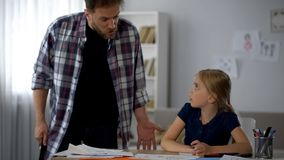 Cruel father shouting at daughter for wrong done homework, threatening to punish. Stock photo stock image