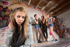 Cruel Gang Bullies Girl. Unhappy blond girl near cruel group of teens Stock Photo