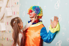 Cruel girl playing with scared clown Stock Photography
