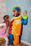 Cruel girl playing with scared clown Royalty Free Stock Photos