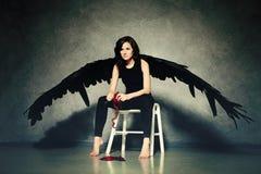 Cruel Love. Woman Black Angel Peeling a Heart Royalty Free Stock Images