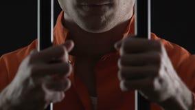 Cruel serial killer holding jail cell bars, prisoner hands closeup, law breaking. Stock footage stock video
