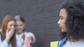 Cruel teen girls laughing at biracial female student, school bullying, racism. Stock footage stock footage