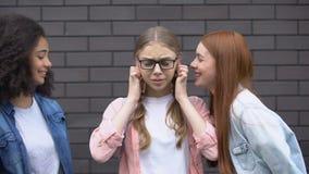Cruel teenagers teasing female pupil eyeglasses, bullying victim covering ears. Stock footage stock video