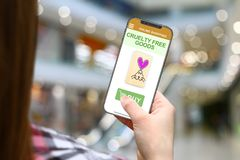 Cruelty free idea, girl with frameless phone on blurred mall background. Cruelty free concept, girl with frameless phone on blurred mall background stock photography