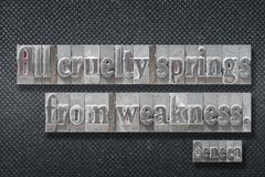 Cruelty springs Seneca. All cruelty springs from weakness - ancient Roman philosopher Seneca quote made from metallic letterpress on dark background royalty free stock images