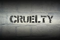 Cruelty word gr. Cruelty stencil print on the grunge white brick wall stock photo