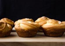 Cruffin - Buns from yeast dough. Dark graunge background. Mystical light. cinnamon craffin cinnabon mix of croissant and muffin Stock Image