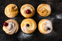 Cruffin - Buns from yeast dough. Dark graunge background. Mystical light. cinnamon craffin cinnabon mix of croissant and muffin Stock Photo