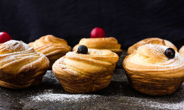 Cruffin - Buns from yeast dough. Dark graunge background. Mystical light. cinnamon craffin cinnabon mix of croissant and muffin Royalty Free Stock Photos
