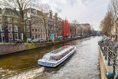 Cruise boat at Amsterdam canals in Holland, street view Royalty Free Stock Photos