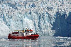 Cruise boat among the icebergs, Greenland. Red and white cruise boat carrying tourists in front of Eqi Glacier several hours North of Ilulissat, Greenland Stock Photography