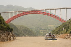 Cruise Boat and the red bridge on Yangtze river. Red bridge and a tourist boat at the bend of Yangtze river, China royalty free stock photo