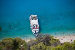 Cruise boat seen from above on clear blue water. With lots of people sunbathing and swimming stock images