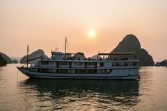 Cruise boat at sunset Halong bay Stock Photos