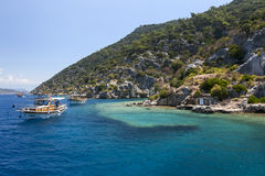 Cruise boats sail past a section of the Sunken City on Kekova Island in Turkey. Stock Images