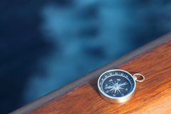 Cruise compass on wooden rail sea Stock Photo