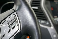 Cruise control buttons on the black leather steering wheel. Of the car Royalty Free Stock Images