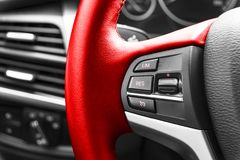 Cruise control buttons on the red steering wheel of a modern car, car interior details. Stock Image