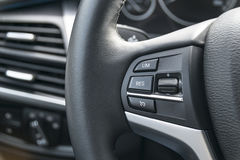 Cruise control buttons on the steering wheel of a modern car, ca. R interior details Royalty Free Stock Photos