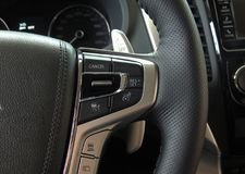 Speed control and mode selectors on the multifunction steering wheel inside a vehicle. Cruise control and speed limiter buttons on the car steering wheel Royalty Free Stock Image