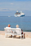 Cruise Couple. Elderly couple on vacation sitting on a bench at the ocean looking at a cruise ship Stock Photos