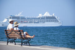 Cruise couple. Couple on vacation (in Crete), Chania sitting on a bench at the mediterranean sea looking at a cruise ship. summer 2011 Stock Photo