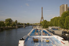 Cruise decks and the Eiffel Tower, Paris. Eiffel Tower on the banks on the River Seine, Paris, France with blue cruise boat decks in the foreground Royalty Free Stock Photo