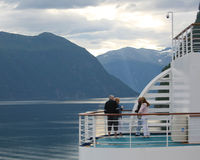 Cruise With Friends. Two couples enjoy a quiet moment on a cruise ship.  Beautiful sunlight reflected on the water during a Norwegian Fjords cruise Stock Images
