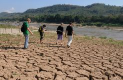 Laos: Cruise guests are walking over dry earth at the Mekong River near Luang Brabang stock image