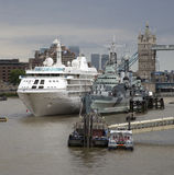 Cruise and historic warship River Thames London UK Stock Photo