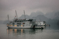 Cruise junk boat sits under early morning fog. Royalty Free Stock Photos
