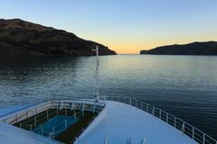 View from the bow of a cruise ship leaving a narrow harbor at dusk royalty free stock photo