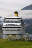 Cruise liner in the Geirangerf. Cruise liner in a fjord with a tent of mountain bikers in the foreground - Norway Royalty Free Stock Images