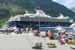 Cruise liner in Geirangerfjord sea port with tourists on June 29, 2016 in Geiranger, Norway. Geirangerfjord is famous place and UNESCO heritage site Stock Photography